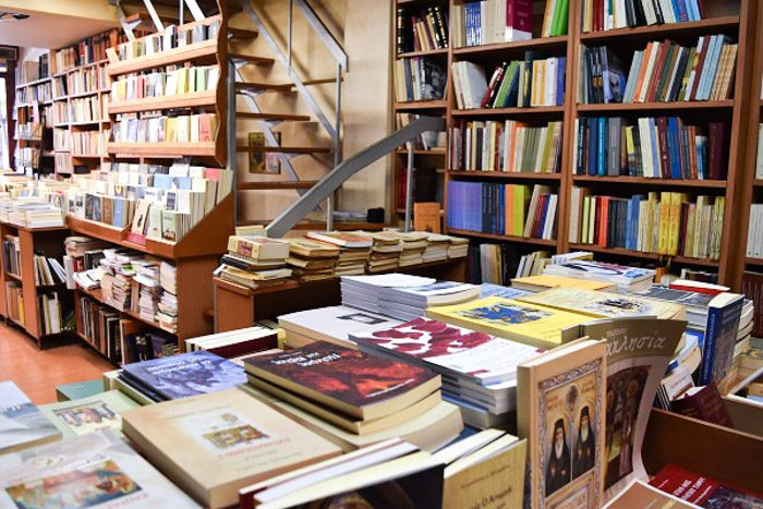 Inside Nautilus Bookstore, Athens, Greece.  Books on wooden shelves line every surface, and a staircase disappears out of sight.