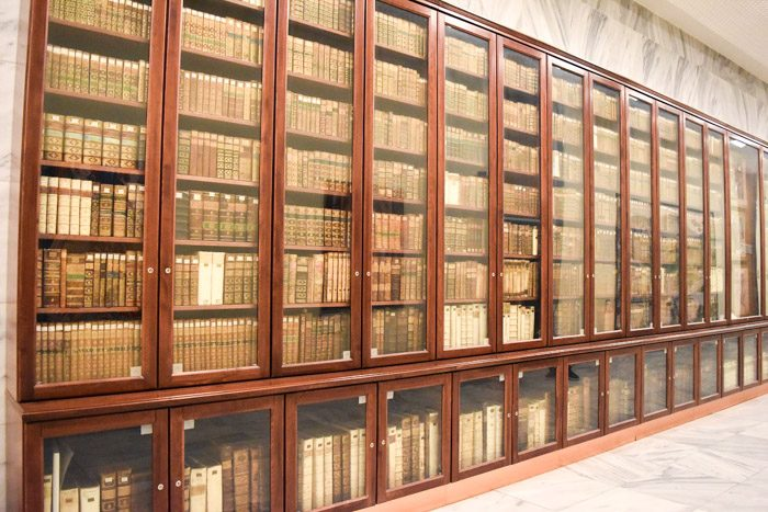 One room of the national library that displays a long row of bookshelves inside glass doors to protect the rare books on display.
