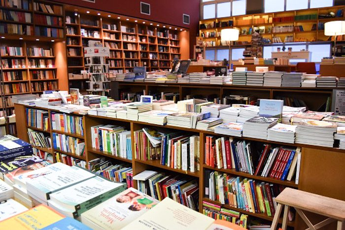 Inside Pataki Bookstore, Athens. Orderly rows of books on wooden shelving fill the room.