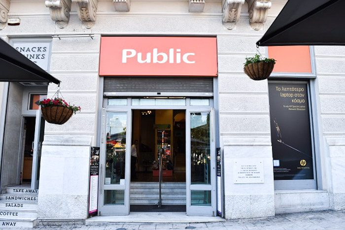 Front of Public, Athens, Greece. An imposing pale stone building with a large rectangular orange 'Public' sign above the open door.