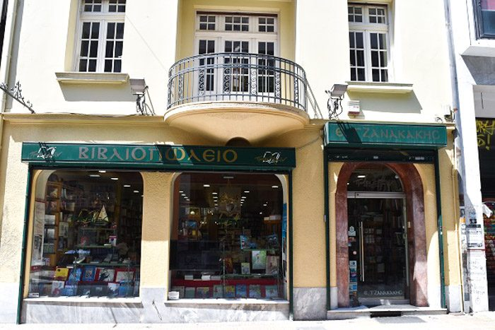 Front of Bookstore E. Tzanakakis Parimin, Athen, Greece. A pale yellow building with dark green signs above the two windows and arched front door. Books can be seen through the windows.
