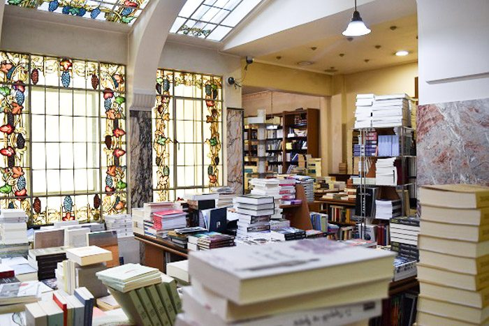 Inside Bookstore E. Tzanakakis Parimin, Athen, Greece. Piles of books fill the foreground. The room has large windows decorated with stained glass in the design of grape vines.