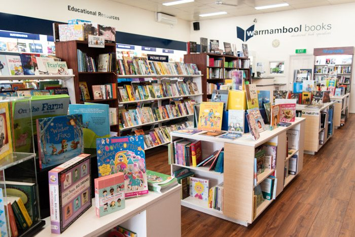 Picture of a long row of shelves from another angle, showing educational books as well as children's books.