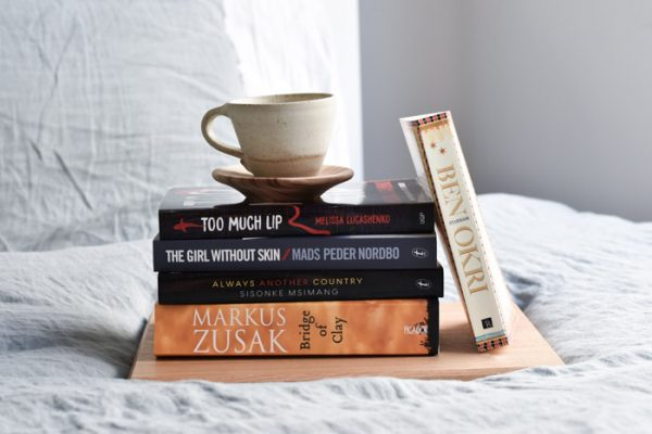 A stack of books on a bed. Bridge of Clay by Marcus Zusak, Always Another Country by Sisonke Msimang, The Girl Without Skin by Mads Peder Nordbo, Too Much Lip by Melissa Lucashenko, Starbook by Ben Okri