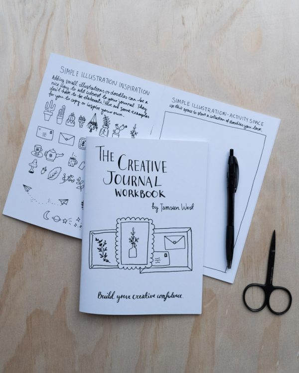 Printed creative journal workbook next to pen and scissors