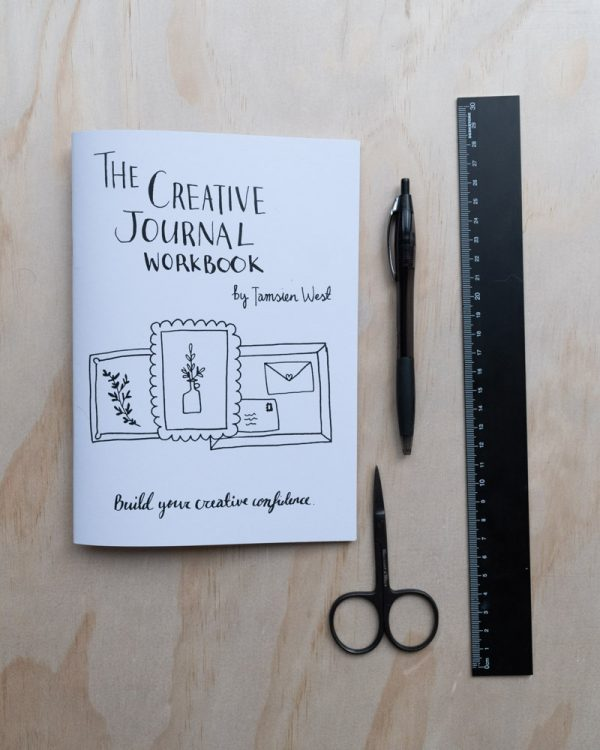 Front cover of the creative journal workbook next to assorted stationery
