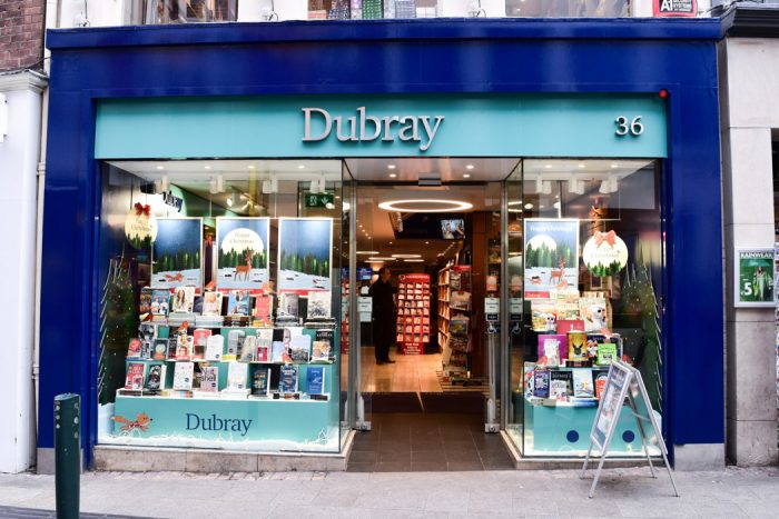 Dubray books shopfront with blue trim and windows opening into a bright-looking bookshop
