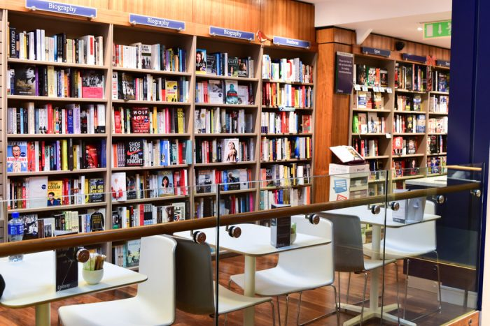 A wall of books and some cafe seating in front of them