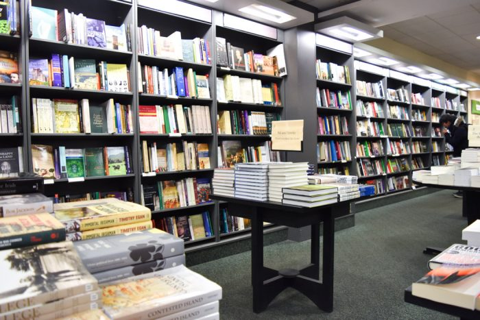 A long wall of books and a small table with more books on display.