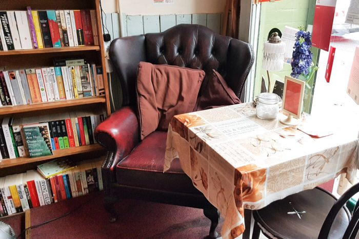 Cozy leather reading chair and small coffee table in the Winding Chair Bookshop
