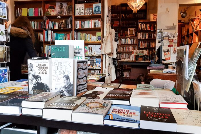 Table stacked with all kinds of books and surrounded by other bookshelves