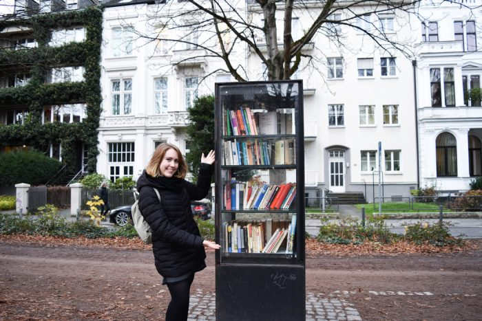Young woman standing next to a cabinet filled with books on the pavement in the city of Bonn