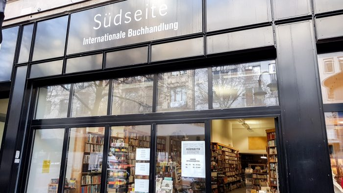 Front of Sudseite bookshop in Frankfurt, with a black exterior and window display visible.