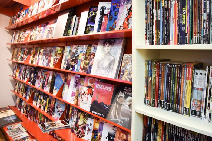 A wall with shelves stocked with a large range of comic books and graphic novels for sale in T3 Terminal Entertainment