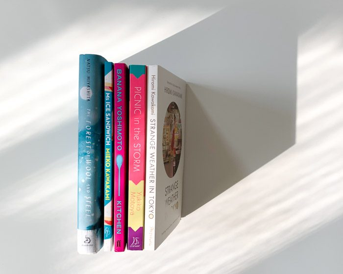 Five books arranged with spines facing up on a white flat background