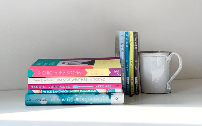 A book stack of five books, lying on their side spines facing towards the viewer, next to Japanese CDs and a coffee mug.