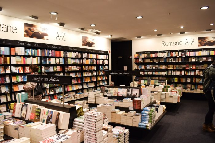 One corner of a bookshop with lots of books for sale on the walls and display tables.