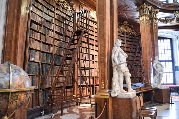 Close up of one of the large wooden bookshelves in the Austrian National Library, with a rolling staircase and two marble statues alongside.
