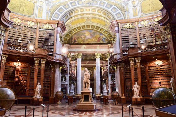 The interior of the Austrian National Library. Marble statue in the centre of the circular room, surrounded by large timber bookshelves, marble columns, and Venetian globes, topped with a domed, painted ceiling.