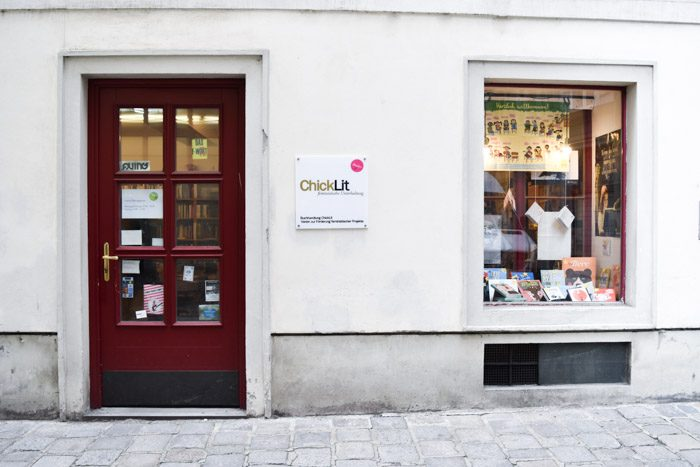 The white shopfront of ChickLit with red door and one large rectangular window.