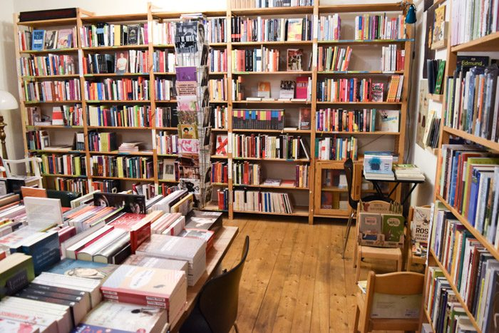 The interior of ChickLit, with wooden floors, large bookshelves and rotating card displays.