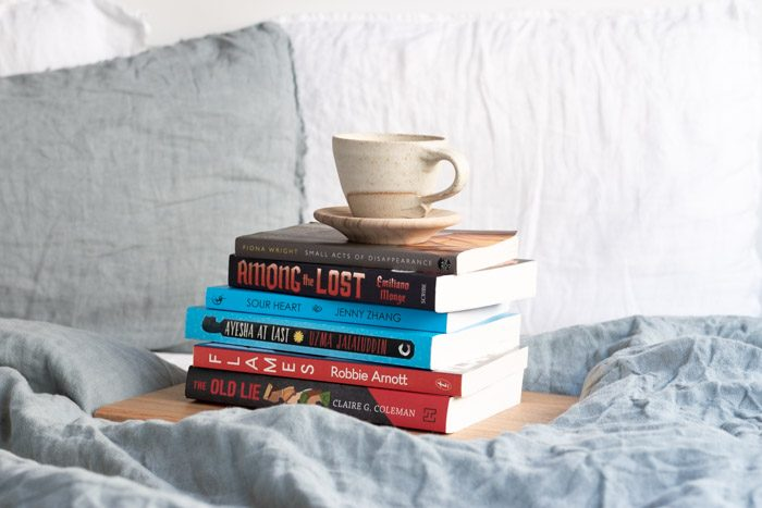 7 Books to Read from Ubud Writers and Readers Festival - Stack of 6 books on a bed with pale blue linen.