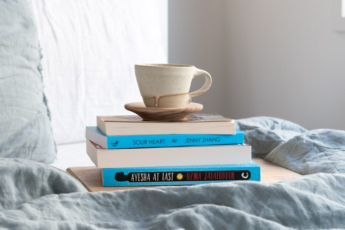 7 Books to Read from Ubud Writers and Readers Festival - Stack of 4 books on a bed with pale blue linen. Visible titles are Sour Heart by Jenny Zhang and Ayesha at Last by Uzma Jalaluddin.