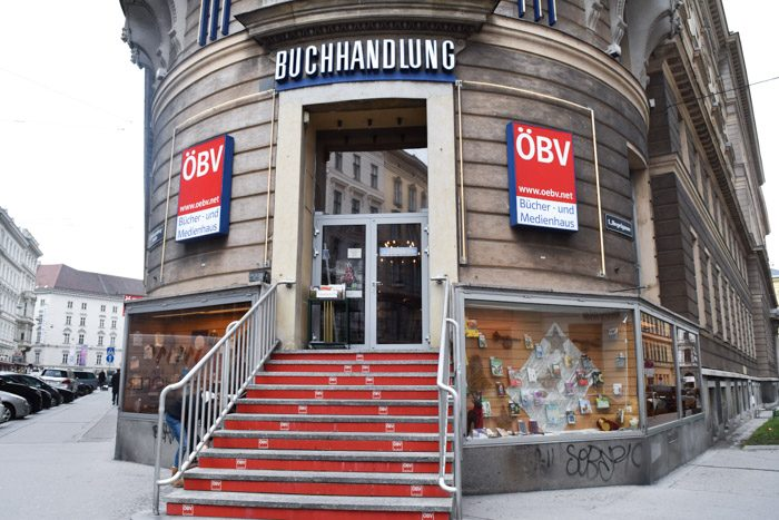 A rounded, period shopfront with the shop's name (Buchhandlung) above the entrance and two signs with the shop's initials (OBV) on either side of the entrance. Stairs lead up to the front door.