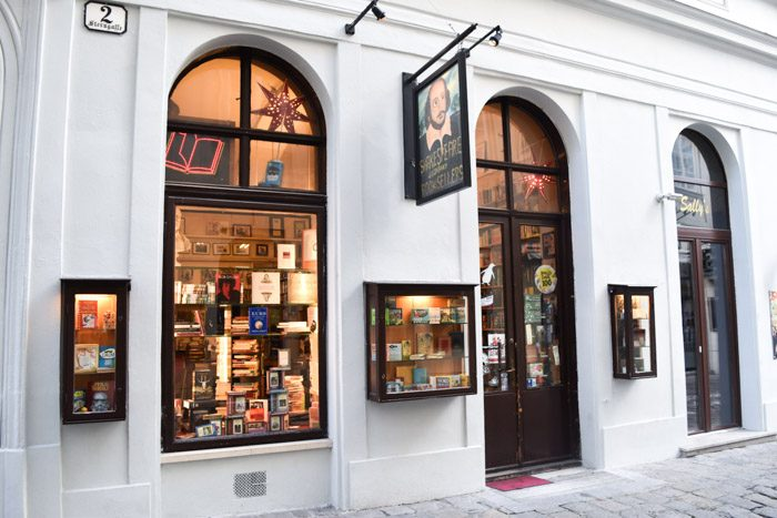 White rendered shopfront with arched windows showing the illuminated interior of Shakespeare and Company Booksellers.