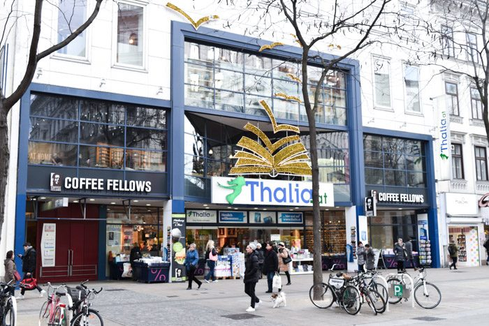 A modern glass 3-storey shopfront, with the shop name (Thalia) in big blue letters on a white background, along with a large decorative 3D image of a book just above it.