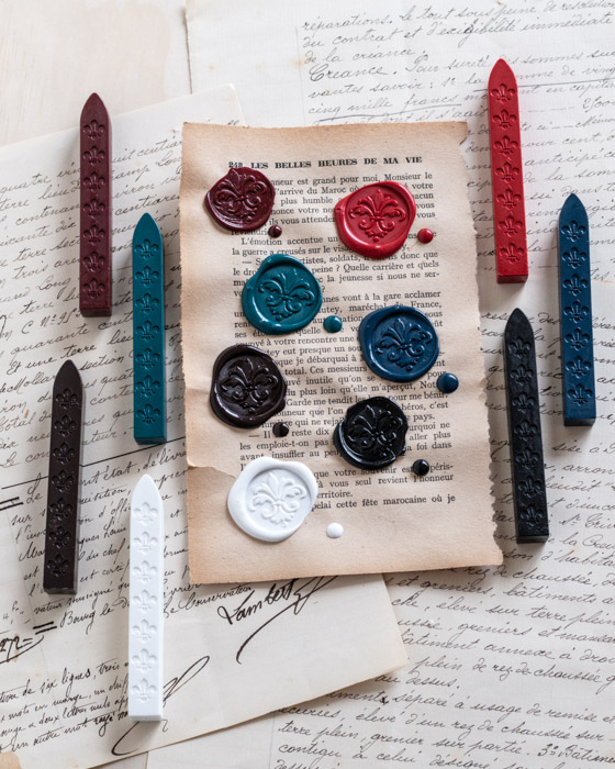 Wickless sealing wax sticks, one stick of each of the following colours is shown: Wine red, Flame red, charcoal black, coffee brown, teal green, ocean blue, and chalk white. On a background of vintage papers.