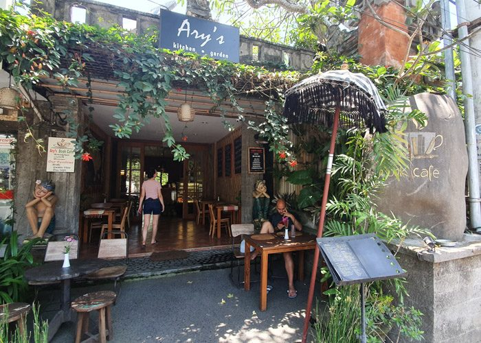 Exterior of Ary's Book Cafe in Ubud, Bali, Indonesia.  A stone builing with a large open entrance covered by green vines. Wooden tables and chairs line both sides of the space.