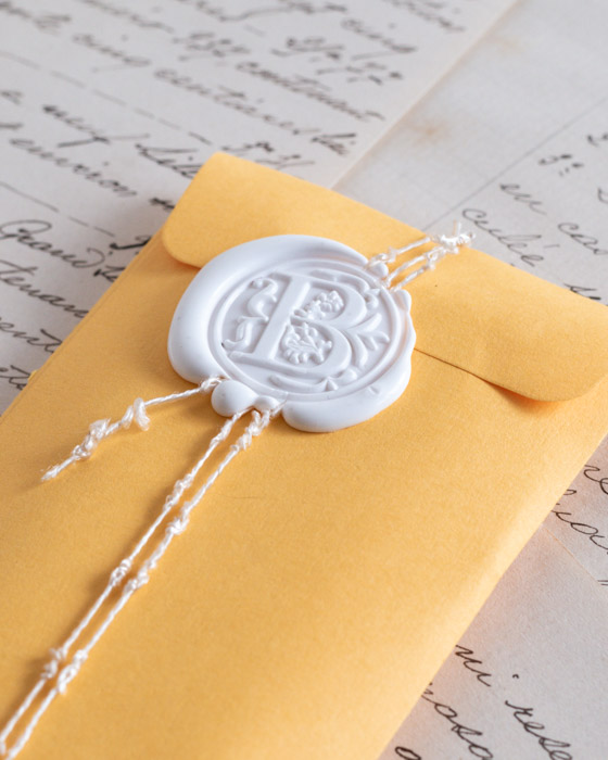 Close up of chalk white wax seal with letter B design, on small yellow envelope.