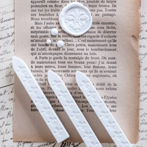Three sticks of chalk white wickless sealing wax with an example wax seal on vintage paper.