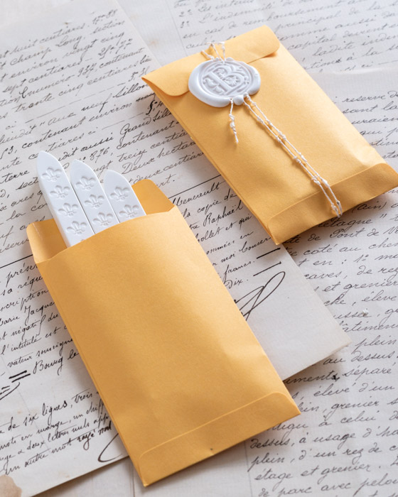 Three sticks of chalk white wickless sealing wax in a small yellow paper pocket, and another yellow paper pocket wrapped in twine and sealed with a wax seal of the same colour.
