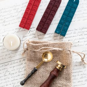 Christmas themed gift set, including a small candle, two each of flame red, wine red, and teal green wickless wax sticks, a wax seal stamp with wooden handle, metal spoon with wooden handle, and hessian gift bag.