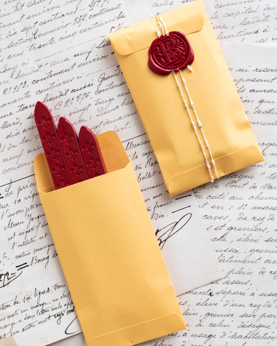 Three sticks of flame red wickless sealing wax in a small yellow paper pocket, and another yellow paper pocket wrapped in twine and sealed with a wax seal of the same colour.