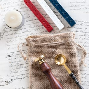 French themed gift set, including a small candle, one each of flame red, chalk white, and ocean blue wickless wax sticks, a wax seal stamp with wooden handle, metal spoon with wooden handle, and hessian gift bag.