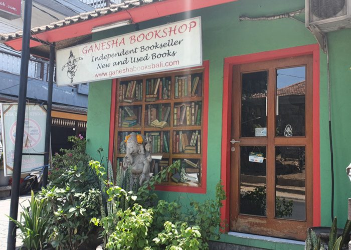 Exterior of Ganesha Bookshop in Ubud, Bali, Indonesia. A small green building with red painted edges around the door and a fake window with books painted on it.
