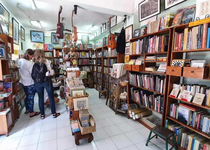 Interior of Ganesha Bookshop in Ubud, Bali, Indonesia. Many wooden shelves are filled with books, 3 guitars hang from the ceiling and three people are browsing on the left.