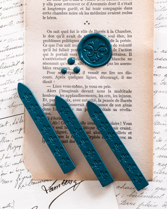 Three sticks of teal green wickless sealing wax with an example wax seal on vintage paper.