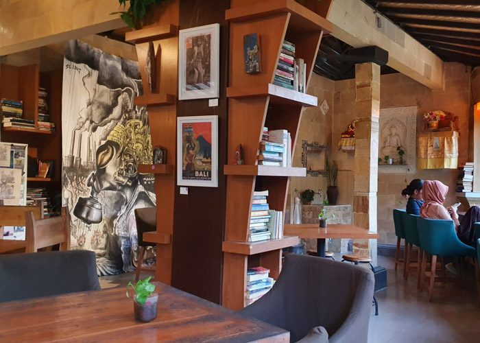 Interior of Little Talks book cafe in Ubud, Bali, Indonesia. Books are stacked on wooden shelves, a large black and white artwork hangs on the rear wall. Two women are sitting in green chairs on the right, under a small alter.