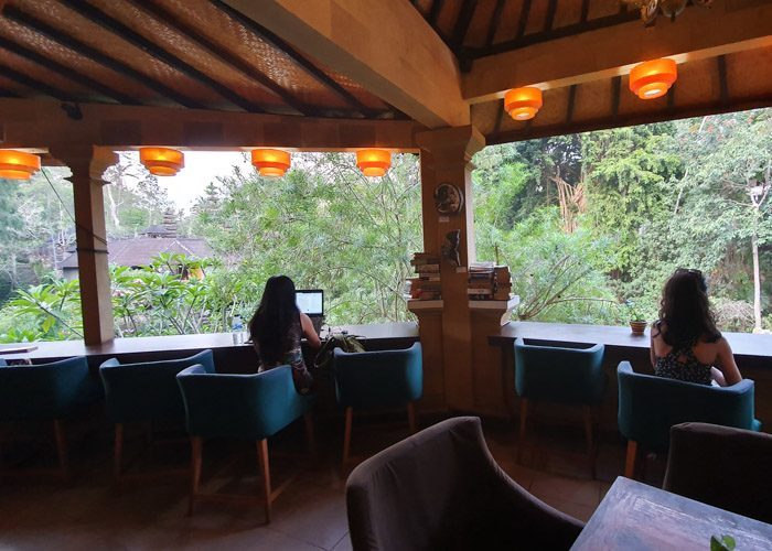 Interior of Little Talks book cafe in Ubud, Bali, Indonesia. Two women sit in green chairs, facing a beautiful view of green trees and a temple in the distance.
