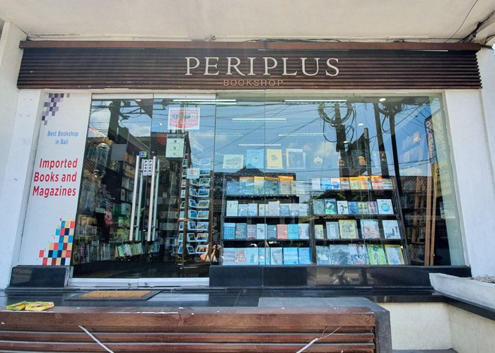 Exterior of Periplus Bookshop in Ubud, Bali, Indonesia. A simple glass fronted shop, with neatly arranged books visible through the window. A wooden sign above the glass says Periplus Bookshop, and a white sign on the left says 'Imported Books and Magazines'.