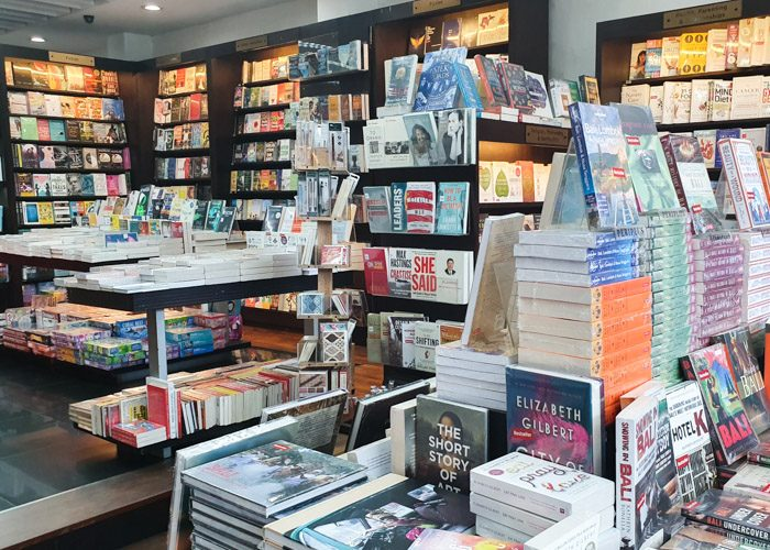 Interior of Periplus Bookshop. Books are neatly stacked on wooden shelves and tables.