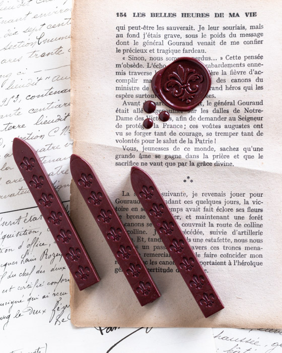 Three sticks of wine red wickless sealing wax with an example wax seal on vintage paper.