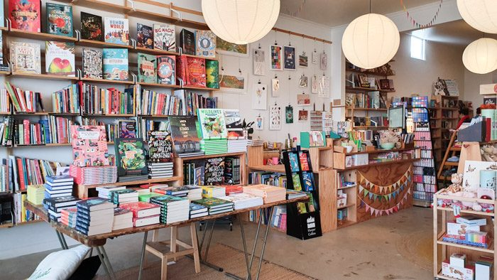 Interior of Squishy Minnie Bookstore in Kyneton. A colourful range of books are displayed on shelves and tables and the counter is decorated with rainbow bunting.