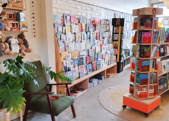 Interior of Squishy Minnie Bookstore in Kyneton. Childrens picture books are displayed on a large shelf with their covers facing forwards. A shelf on the left displays stuffed animal toys above a green indoor plant and a green armchair.