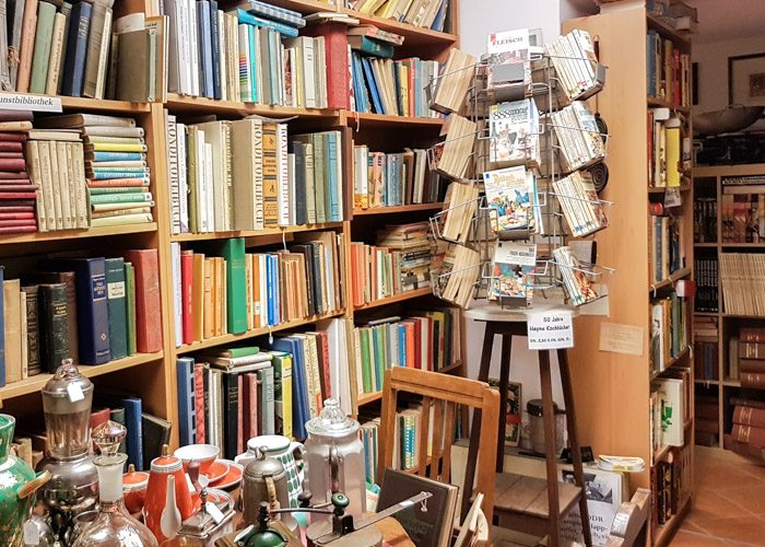 One corner of this bookstore filled with a large range of secondhand books stacked on bookshelves and a tea set on a table.