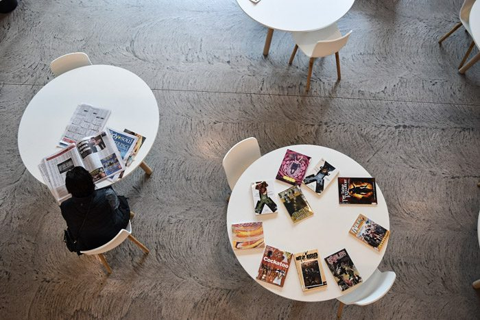 Geelong Library interior, round white tables are seen from above. A person sits at one table reading a newspaper, another table has an array of graphic novels spread on it.